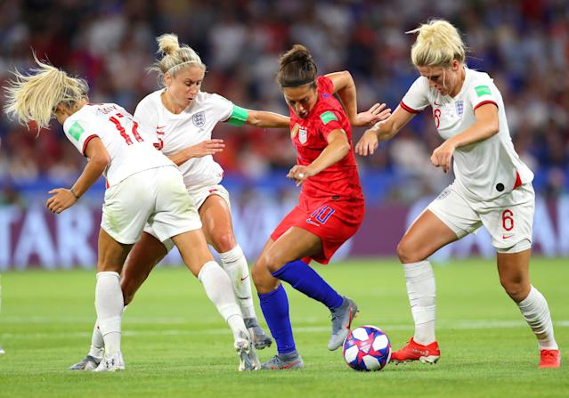 Carli Lloyd of the USA is challenged by Rachel Daly, Steph Houghton, and Millie Bright of England during the 2019 FIFA Women's World Cup France Semi Final match between England and USA at Stade de Lyon on July 02, 2019 in Lyon, France. (Photo by Catherine Ivill - FIFA/FIFA via Getty Images)