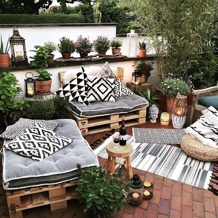 summery cushions and throw pillows set over wooden palettes give your yard a wonderfully bohemian feel.
