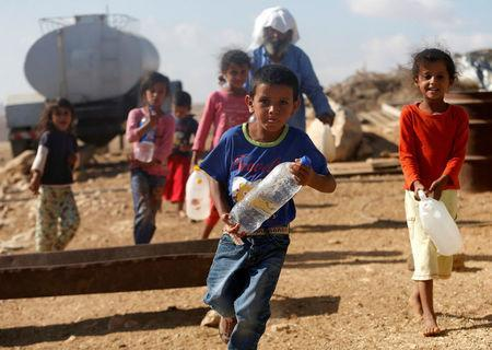 Palestinian children carry water bottles near their house on the outskirts of the West Bank village of Yatta, south of Hebron, August 17, 2016. REUTERS/Mussa Qawasma
