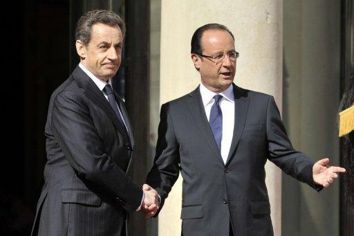 Nicolas Sarkozy (left) welcomes Francois Hollande at the Elysee Palace