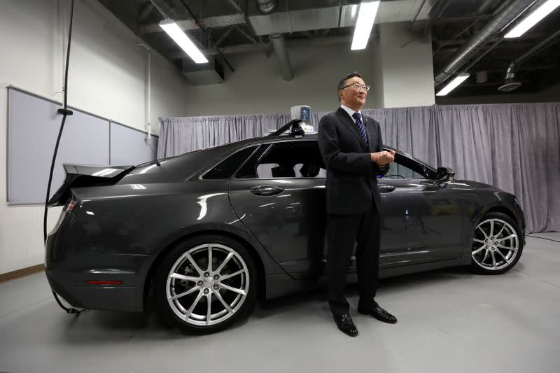 Blackberry CEO Chen stands in front of an autonomous vehicle at the BlackBerry QNX headquarters in Ottawa