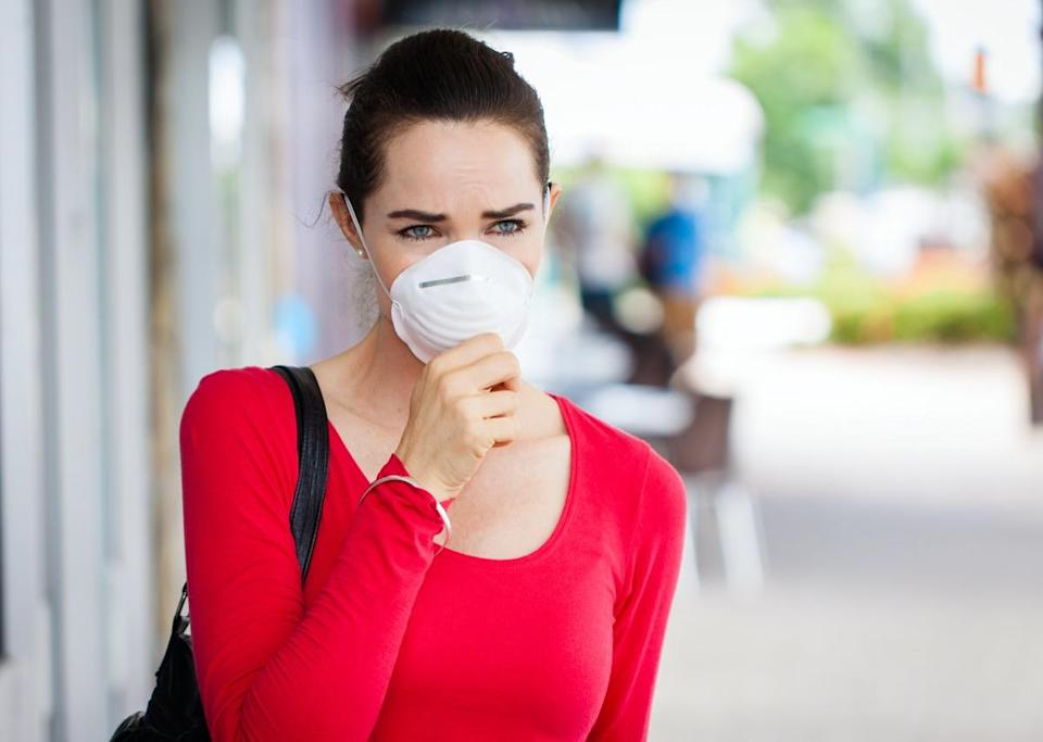 A woman wearing a face mask in the city coughing.