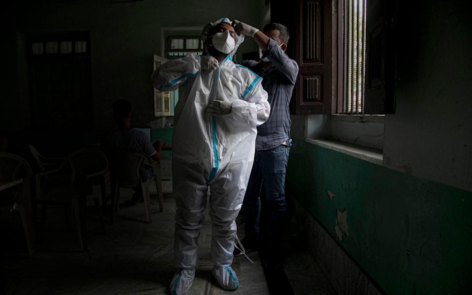 An Indian health worker helps another wear protective gear before proceeding to take nasal swab samples to test for COVID-19 - AP Photo/Anupam Nath