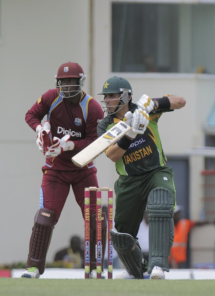 Pakistan batsman Misbah-ul-Haq drives on his way to a half century during the 3rd ODI West Indies v Pakistan at Beausejour Cricket Ground in Gros Islet on July 19, 2013. The wicket-keeper is Johnson Charles. Pakistan made 229-6 off their 50 overs in the third one-day international against the West Indies.    AFP PHOTO/Randy Brooks        (Photo credit should read RANDY BROOKS/AFP/Getty Images)