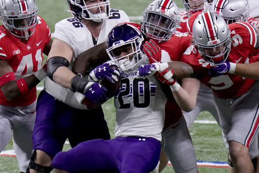 Northwestern running back Cam Porter (20) struggles for yardage during the first half of the Big Ten championship NCAA college football game against Ohio State, Saturday, Dec. 19, 2020, in Indianapolis. (AP Photo/AJ Mast)