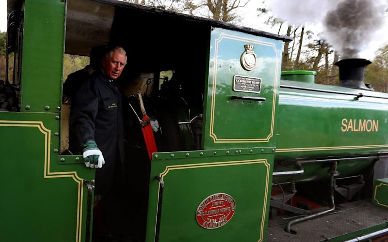 The Prince of Wales drives a steam train during his visit to the Royal Deeside Railway in Banchory - PA