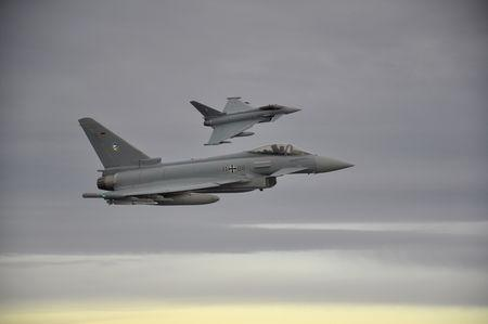 Two German Eurofighter jets simulate the interception of a plane over the Baltic sea