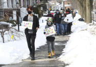 Nicklas Bare, 16, left, and his brother Joshua,11, of Warren, Mich., walk north on Wayburn St. during the walking rally to protest hate and racism, Sunday, Feb. 21, 2021 in Grosse Pointe Park, Mich., following a white resident's display of a Ku Klux Klan flag in a side window facing their Black neighbor's home. JeDonna Dinges, 57, of Grosse Pointe Park, said the klan flag was hanging next door in a window directly across from her dining room. The incident occurred two weeks ago. (Clarence Tabb, Jr./Detroit News via AP)