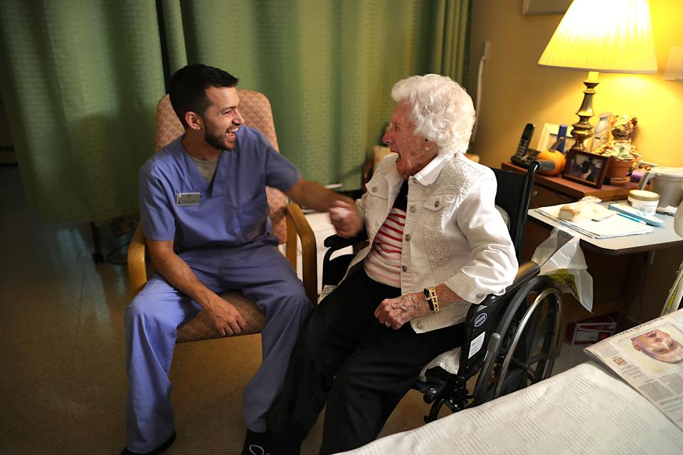 CHATHAM, MA - NOVEMBER 5: Nurses aid Nick Burrill shares a laugh with Broad Reach resident Laurie Hill, 101, in her room in Chatham, MA on Nov. 5, 2019. Struggling to find workers for his nursing home and assisted-living center in this seaside tourist town, Bill Bogdanovich tried a new strategy: buying properties on the southeastern elbow of Cape Cod to rent to employees like Burrill. He offered below-market rents to workers, many recruited from off the Cape and as far away as Puerto Rico, who were having trouble finding places to live. A year later, his gambit appears to have paid off: Bogdanovich has been able to hire and retain more workers - the better for his senior housing residents, and for business. (Photo by John Tlumacki/The Boston Globe via Getty Images)