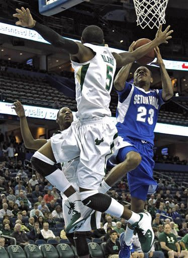 Seton Hall guard Fuquan Edwin (23) goes to the basket between South Florida defenders Jawanza Poland (5) and Hugh Robertson (34) during the first half of an NCAA college basketball game, Friday Jan. 13, 2012, in Tampa, Fla. (AP Photo/Chris O'Meara)