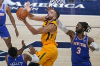 Utah Jazz center Rudy Gobert, center lays the ball up as New York Knicks' RJ Barrett, left, and Nerlens Noel (3) defend in the second half during an NBA basketball game Tuesday, Jan. 26, 2021, in Salt Lake City. (AP Photo/Rick Bowmer)