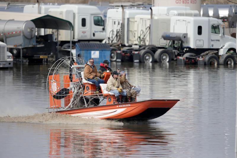 Gabe Schmidt, owner of Liquid Trucking, top right, travels by air boat with Glenn Wyles, top left, Mitch Snyder, bottom left, and Juan Jacobo, bottom right, as they survey damage from the flood waters of the Platte River, in Plattsmouth, Neb., Sunday, March 17, 2019.