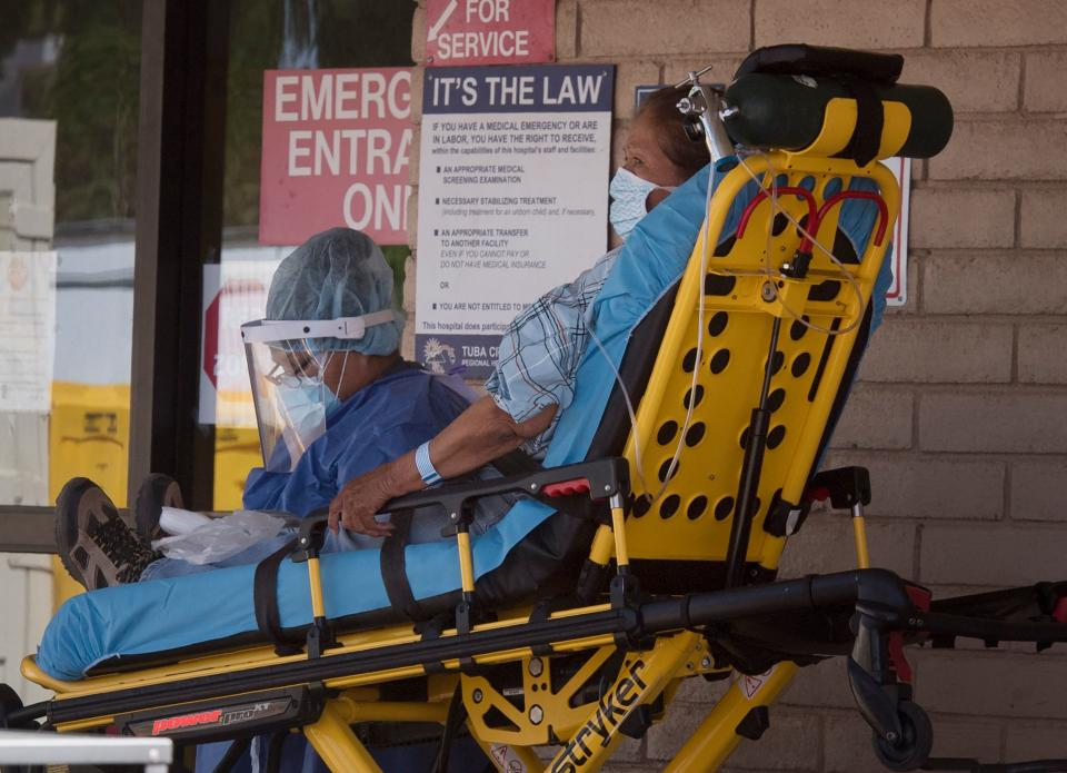 A patient is taken from an ambulance to the emergency room of a hospital in the Navajo Nation town of Tuba City during the 57 hour curfew, imposed to try to stop the spread of the Covid-19 virus through the Navajo Nation, in Arizona on May 24, 2020 - Weeks of delays in delivering vital coronavirus aid to Native American tribes exacerbated the outbreak, the president of the hard-hit Navajo Nation said, lashing the administration of President Donald Trump for botching its response. Jonathan Nez told AFP in an interview that of the $8 billion promised to US tribes in a $2.2 trillion stimulus package passed in late March, the first tranche was released just over a week ago. (Photo by Mark RALSTON / AFP) (Photo by MARK RALSTON/AFP via Getty Images)
