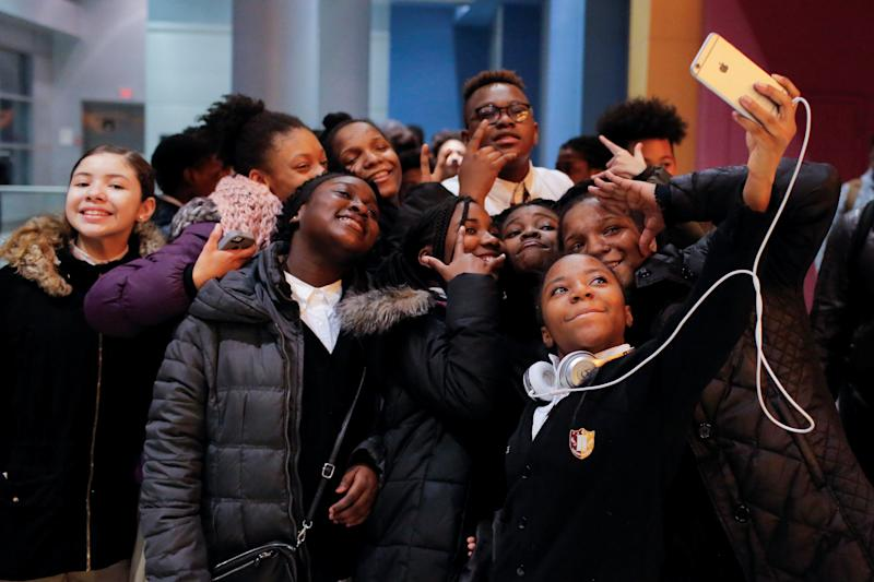 "A group of children takes a selfie as they arrive on the opening night of the film ""Black Panther"" at the AMC Magic Johnson Harlem 9 cinemas in Manhattan, New York, on Feb. 15, 2018."