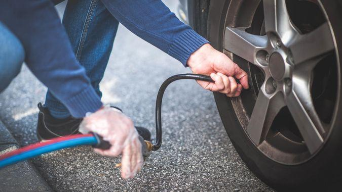 Man checking pressure and inflating car tire.