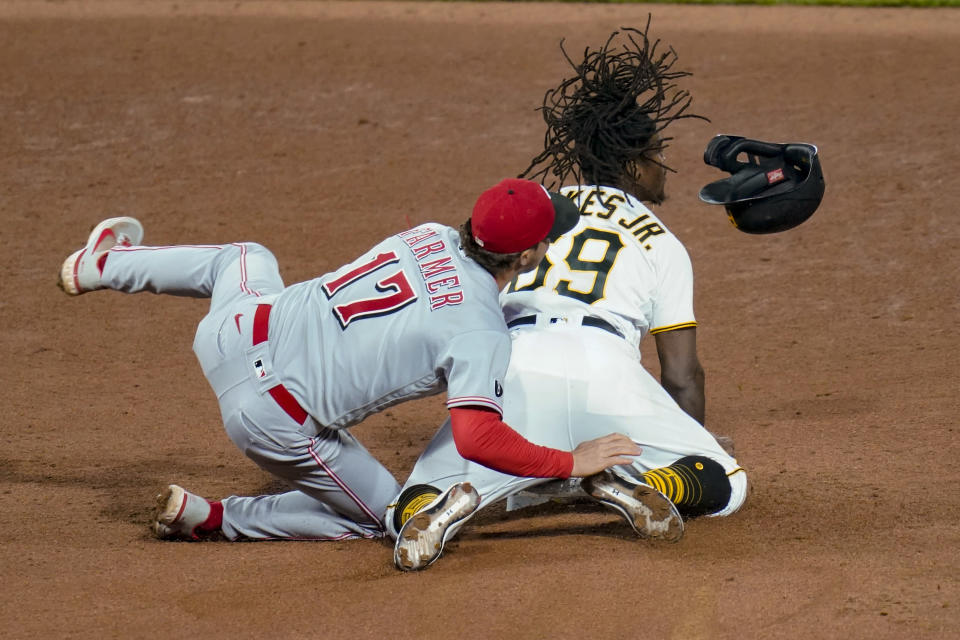 Pittsburgh Pirates' Troy Stokes Jr. , right, loses his helmet as Cincinnati Reds shortstop Kyle Farmer tumbles over him as Stokes stole second during the sixth inning of a baseball game Tuesday, May 11, 2021, in Pittsburgh. (AP Photo/Keith Srakocic)