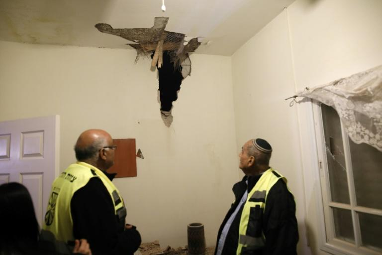 Israeli volunteer rescuers check damage in house in the southern Israeli town of Sderot, caused by a rocket fired from the Gaza Strip on March 25, 2019