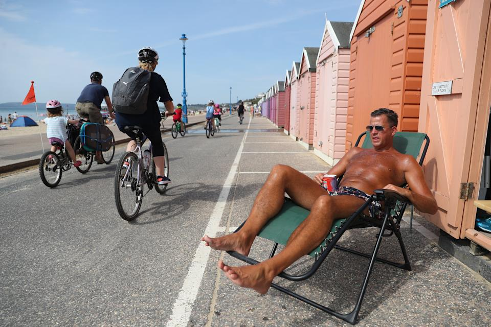 Stuart (no surname given) enjoy the hot weather outside a beach hut at Bournemouth beach in Dorset. (Photo by Andrew Matthews/PA Images via Getty Images)