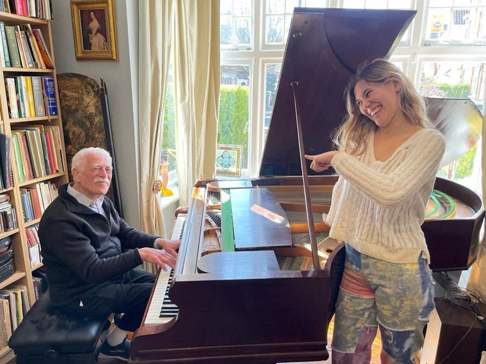 Alan Melinek playing the piano with his granddaughter Bella