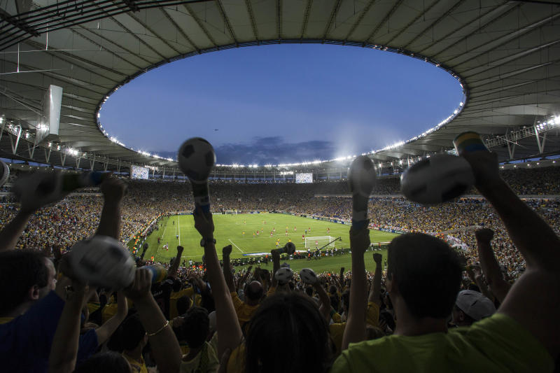 Fans celebrate after Brazil's Fred scored against England during a friendly soccer game at the Maracana stadium, in Rio de Janeiro, Brazil, Sunday June 2, 2013. The game was only given the green light to go ahead after a judge overruled a previous court order which had suspended the match over concerns about the safety of the expensively-upgraded Maracana stadium. The chaos of the on-again, off-again match raises questions about Brazil's readiness to host the Confederation Cup - which opens in two weeks - and next year's World Cup, not to mention the 2016 Rio de Janeiro Olympic Games.(AP Photo/Felipe Dana)