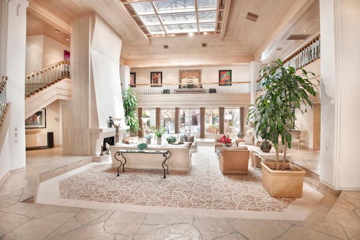 """<p>As you enter the main residence, you can see beyond the great room to the rocky-looking pool area beyond. Upstairs is a gallery. (All photos via <a href=""""http://bit.ly/1OjQdjg"""" rel=""""nofollow noopener"""" target=""""_blank"""" data-ylk=""""slk:Concierge Auctions listing"""" class=""""link rapid-noclick-resp"""">Concierge Auctions listing</a>)<br></p>"""