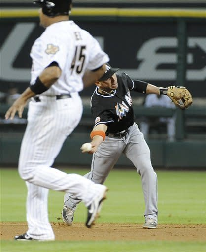 Miami Marlins second baseman Omar Infante throws wide to first base after bobbling the ball, allowing the Houston Astros to score two runs, as Astros' Carlos Lee heads to second in the sixth inning of a baseball game Tuesday, May 8, 2012, in Houston. Infante received two errors on the play. The Astros won 3-2. (AP Photo/Pat Sullivan)