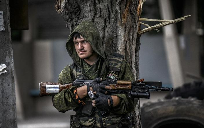A pro-Russian separatist holds his gun as he takes cover behind a tree at a checkpoint in the northern outskirts of city of Donetsk, on July 22, 2014 (AFP Photo/Bulent Kilic)