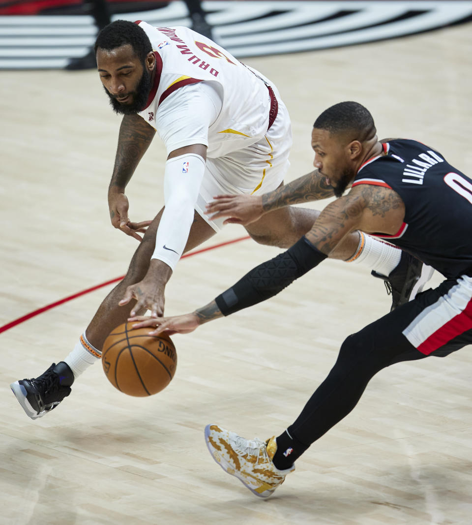 Cleveland Cavaliers center Andre Drummond, left, and Portland Trail Blazers guard Damian Lillard reach for the ball during the second half of an NBA basketball game in Portland, Ore., Friday, Feb. 12, 2021. (AP Photo/Craig Mitchelldyer)