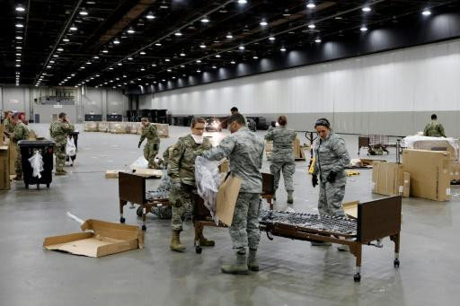 Michigan National Guard troops help put together hospital beds at the TCF Center in Detroit