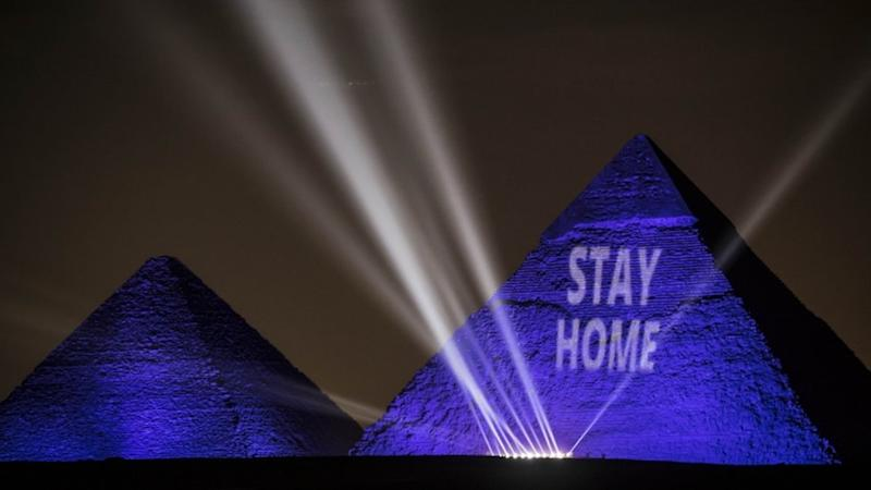 "The pyramids are illuminated in blue with the message ""stay home"" in white lettering."