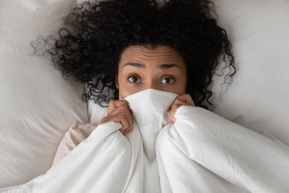 Surprised scared funny african girl lying in bed covering face with blanket, young black woman awake from sleep hiding peeking from duvet feel shy afraid or bad dream nightmare embarrassed, top view