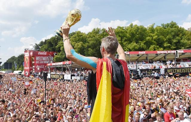 Bastian Schweinsteiger cheers celebrates Germany's victory in the World Cup at Berlin's Brandenburg Gate on July 15, 2014 (AFP Photo/Markus Gilliar)