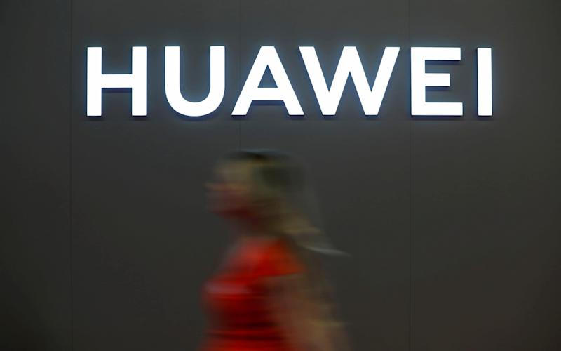 A woman walks in front of the Huawei logo during during the 'Electronics Show at Ptak Warsaw Expo in Nadarzyn, Poland. May 10, 2019.  - REUTERS