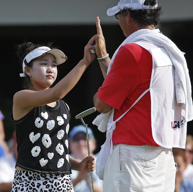 Lucy Li, left, gets a high-five from her caddie, Bryan Bush, right, after finishing her round during the second round of the U.S. Women's Open golf tournament in Pinehurst, N.C., Friday, June 20, 2014. (AP Photo/John Bazemore)