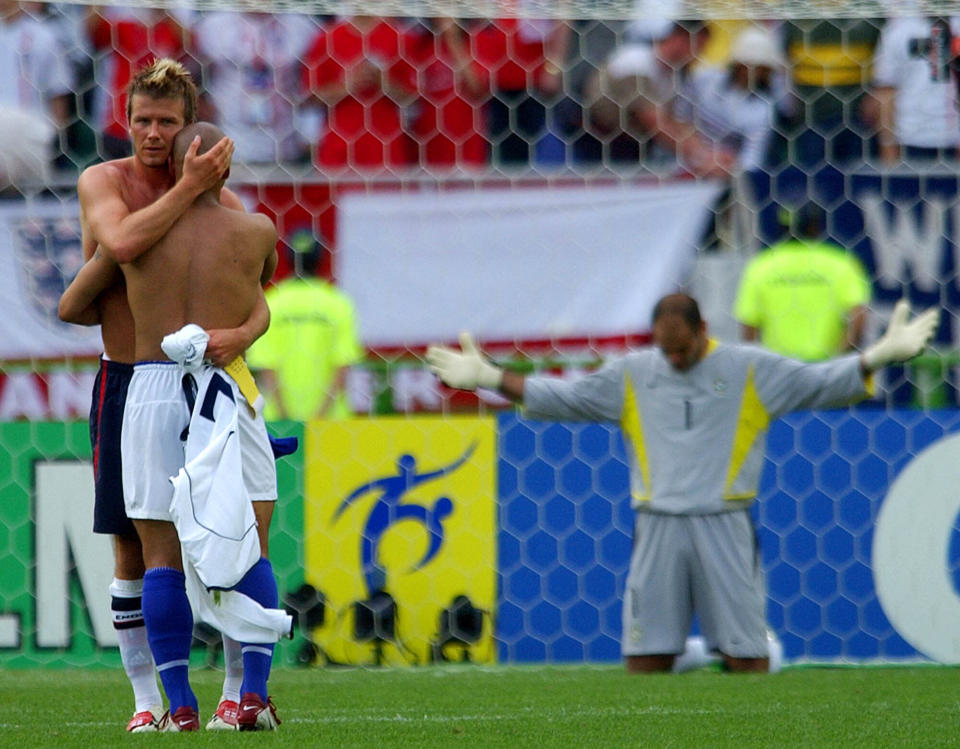 FILE - In this June 21, 2002 file photo England soccer team captain David Beckham embraces Brazil's Roberto Carlos as Brazil's goalkeeper Marcos falls to his knees at the end of their 2002 World Cup quarterfinal soccer match in Shizuoka, Japan. Brazil won the match 2-1. (AP Photo/Dusan Vranic, File)