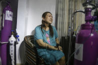 Maricar Tajo, 46, who is from the Philippines but moved to Nigeria in 2007 for work, receives oxygen from a private medical service at her house as she recovers from COVID-19 in Lagos, Nigeria Saturday, Feb. 6, 2021. She was resuscitated after falling unconscious in a hospital intensive care unit when her oxygen saturation levels dropped. (AP Photo/Sunday Alamba)