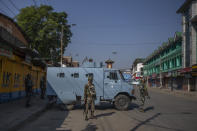 Paramilitary soldiers stand guard on a deserted street on the first anniversary of India's decision to revoke the disputed region's semi-autonomy, in Srinagar, Indian controlled Kashmir, Wednesday, Aug. 5, 2020. Last year on Aug. 5, India's Hindu-nationalist-led government of Prime Minister Narendra Modi stripped Jammu-Kashmir of its statehood and divided it into two federally governed territories. Late Tuesday, authorities lifted a curfew in Srinagar but said restrictions on public movement, transport and commercial activities would continue because of the coronavirus pandemic. (AP Photo/ Dar Yasin)