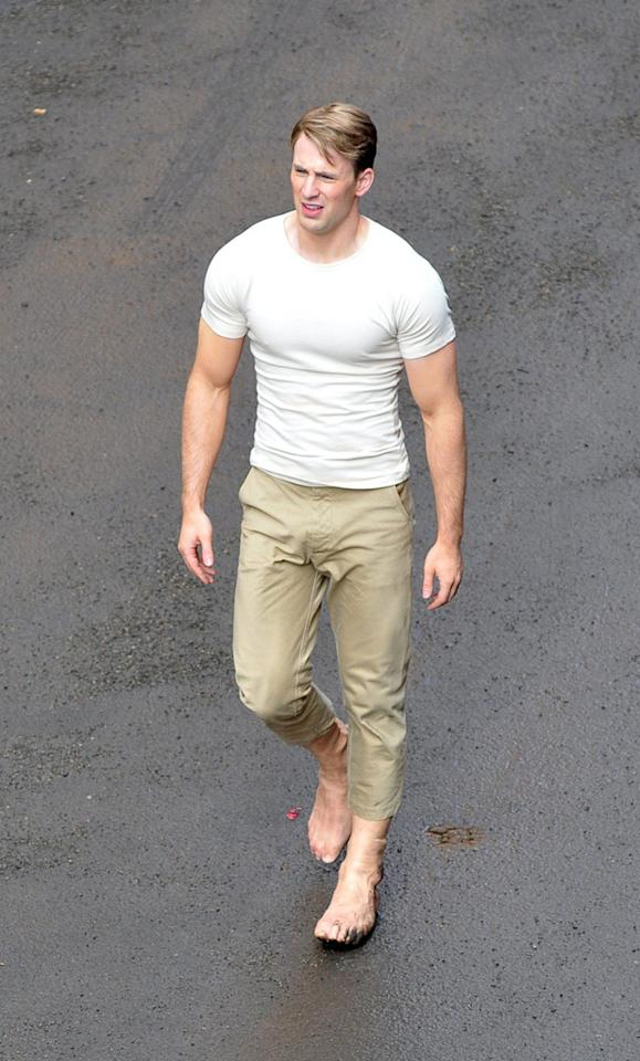 "Photographers in London caught the first shots of <a href=""http://movies.yahoo.com/movie/contributor/1803006988"">Chris Evans</a> filming ""<a href=""http://movies.yahoo.com/movie/1810026349/info"">Captain America: The First Avenger</a>."" Evans has longer and much lighter blond hair than he usually sports, and he's bulked up considerably to play the superhero. Also unusual are the fake feet he's wearing so it looks like he's barefoot without risking injury. Click ahead to see more shots of the star at work, plus a sneak peek at Captain America's costume."
