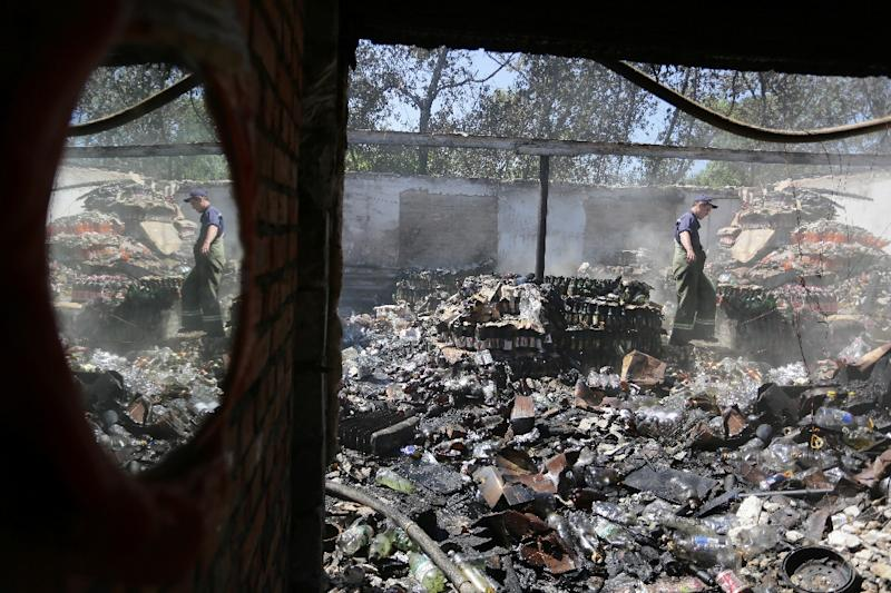 A rescuer is reflected in a mirror as he stands in a food storage unit destroyed as a result of shelling between Ukrainian forces and pro-Russian separatists in the town of Gorlivka on August 3, 2015 (AFP Photo/Aleksey Filippov)