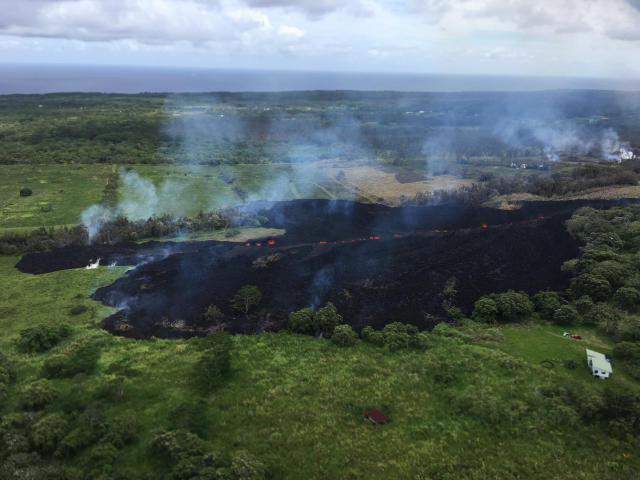 <p>In this May 13, 2018 photo released by the U.S. Geological Survey, gases rise from a fissure near Pahoa, Hawaii. The new fissure in Hawaii's Puna District sent gases and lava exploding into the air, spurring officials to call for more evacuations as residents waited for a possible major eruption at Kilauea volcano's summit. (Photo: U.S. Geological Survey/AP) </p>
