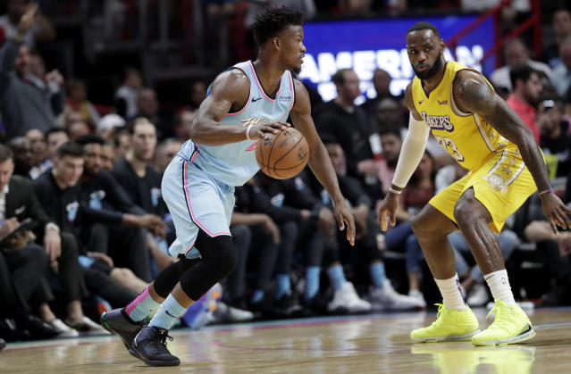 Miami Heat forward Jimmy Butler, left, drives to the basket as Los Angeles Lakers forward LeBron James (23) defends during the first half of an NBA basketball game, Friday, Dec. 13, 2019, in Miami. (AP Photo/Lynne Sladky)