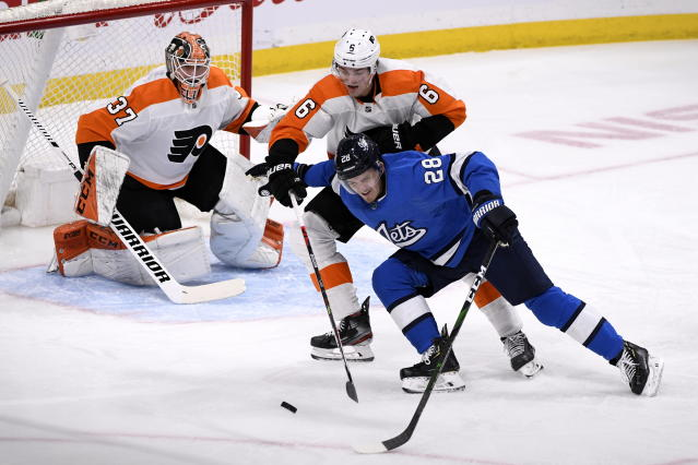 Winnipeg Jets' Jack Roslovic (28) tries to skate around Philadelphia Flyers' Travis Sanheim (6) to shoot against Flyers goaltender Brian Elliott (37) during first-period NHL hockey game action in Winnipeg, Manitoba, Sunday, Dec. 15, 2019. (Fred Greenslade/The Canadian Press via AP)