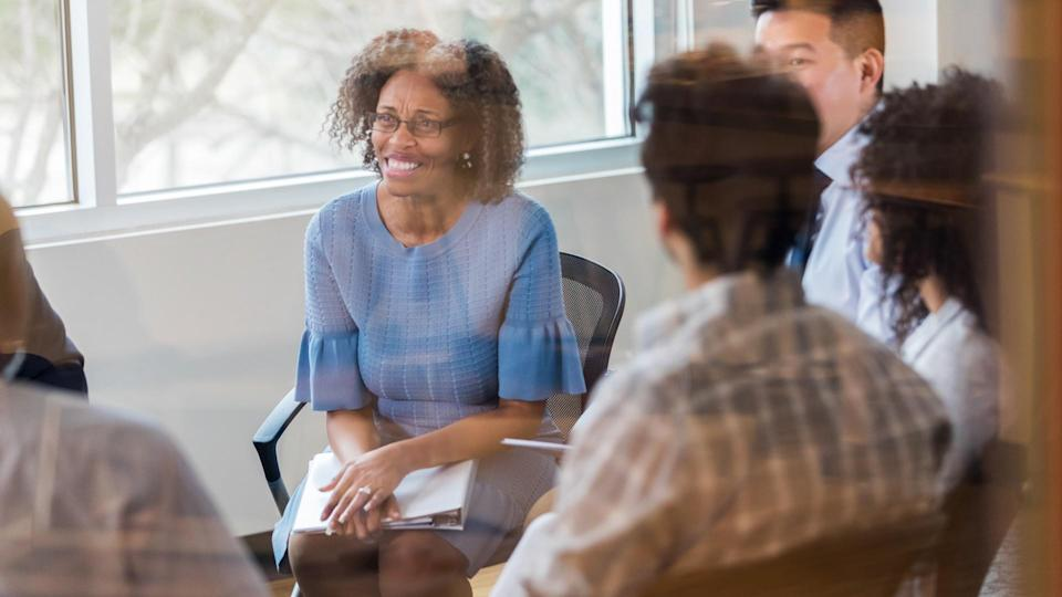 Cheerful mature African American manager smiles while listening to a colleague during a weekly staff meeting.