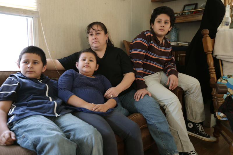 In this Feb. 28, 2013 photo, Sarah Chavez, second from right, sits with her son Bidal, right, daughter Sarahi, second from left, and son Jorge, left, at their home in Lexington, N.C. Desperate to raise money for their 6-year-old daughter's cancer treatments last summer, friends told Jose and Sarah Chavez of a way to quickly turn their meager savings into a small fortune. But what the Chavez family and many others didn't know was that state and federal regulators for months had received complaints that ZeekRewards was a scam. (AP Photo/Chuck Burton)