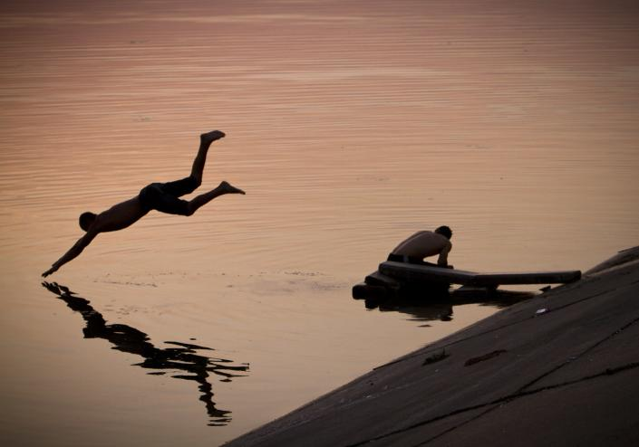 A man dives at sunset in a lake at the end of an unusually hot day in Bucharest, Romania, Wednesday, Aug. 24, 2011. Temperatures climbed to 35 degrees Centigrade in many regions across Romania as a heat wave affects the Balkans region. (AP Photo/Vadim Ghirda)