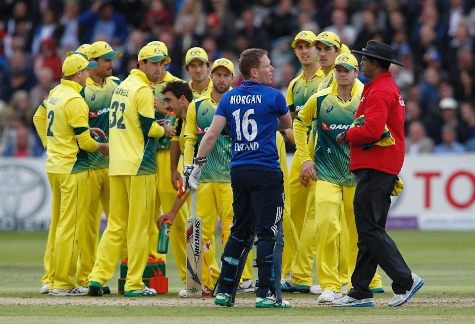 """Australian players look on as England captain Eoin Morgan (C) and counterpart Steven Smith exchange words with the umpire following the dismissal of England''s Ben Stokes for """"obstructing the field"""" at Lord's on September 5, 2015 (AFP Photo/Ian Kington)"""