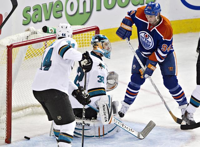 San Jose Sharks' Marc-Edouard Vlasic (44) and Edmonton Oilers' Ryan Smyth (94) watch the puck cross the goal line as goalie Alex Stalock (32) looks for the puck during the second period of an NHL hockey game Friday, Nov. 15, 2013, in Edmonton, Alberta. (AP Photo/The Canadian Press, Jason Franson)