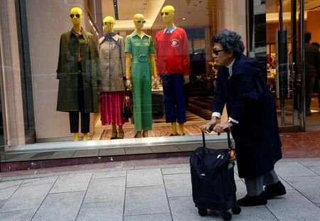 A woman walks past a luxury brand store show window at a shopping district in Tokyo, Japan March 7, 2018. REUTERS/Kim Kyung-Hoon/Files