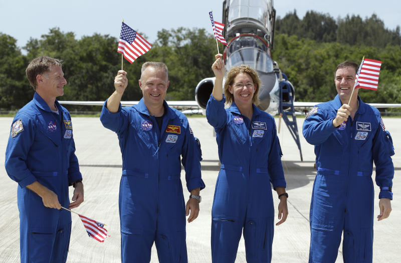 STS-135 commander Chris Ferguson, left, looks on as fellow crew members, from left, pilot Doug Hurley, mission specialist Sandy Magnus, and mission specialist Rex Walheim, wave American flags after arriving at the Kennedy Space Center in Cape Canaveral, Fla., Monday, July 4, 2011.  Space shuttle Atlantis, and her crew of four astronauts, is scheduled to lift off Friday morning on an 12-day mission to the international space station.  The launch will bring an end to NASA's shuttle program. (AP Photo/Chris O'Meara)