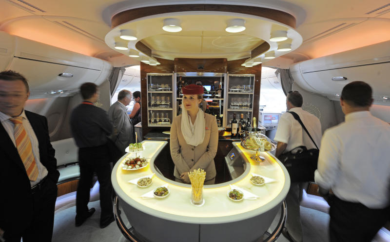 FILE- In this July 13, 2010, file photo Nadine Schumacher, center, works at the bar in the first class section on board Airbus A380 passenger plane of Emirates Airline during the International Air Show ILA at Schoenefeld airport in Berlin. European plane maker Airbus said Thursday, Feb. 14, 2019, that it will stop making its superjumbo A380 in 2021 for lack of customers, abandoning the world's biggest passenger jet and one of the aviation industry's most ambitious and most troubled endeavors. (AP Photo/Jens Meyer, File)